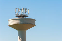 Water tank tower surmounted with a telephone repeater antennas Royalty Free Stock Photography