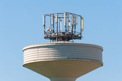 Water tank tower surmounted with a telephone repeater antennas Stock Images