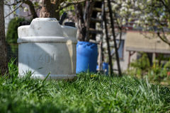 Water tank for watering the grass. Container to retain rainwater in the garden. White plastic jerrycan. Gallon water reserve Stock Photos