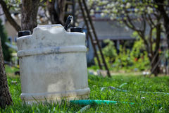 Water tank for watering the grass. Container to retain rainwater in the garden. White plastic jerrycan. Gallon water reserve Royalty Free Stock Image