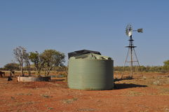 Water tank and windmill in Australian outback with birds in tree ranch station Royalty Free Stock Photos