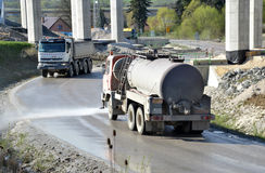 Water tanker splashes water on the road to prevent dust on work site. Stock Image