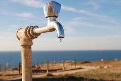 Water tap. With one drop, at the front of blue sky and sea Royalty Free Stock Photos
