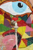 Water tap. On a painted wall with running water Royalty Free Stock Photo