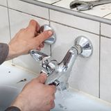 Water tap. Plumber hands fixing water  tap with leaking water Royalty Free Stock Photos