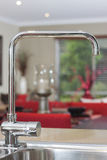 Water tap. Photo of the kitchen water tap with blurred living area as a background Royalty Free Stock Photos