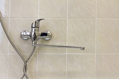 Water tap, chrome stainless metal faucet connected to shower stall tiled wall, mixer cold hot water on blurred bathroom copy space. Background. Modern home royalty free stock photos