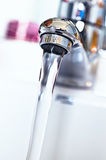 Water tap with flowing water in the bathroom Stock Photography