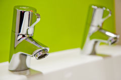 Water tap with a fresh coloured green background Royalty Free Stock Image