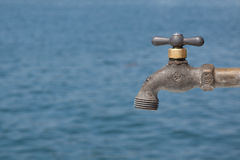 Water tap in front of blue backround Royalty Free Stock Photography