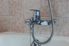 Water tap with a hose from the shower over the bath. In the bathroom stock photos