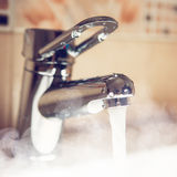 Water tap with hot water steam. Closeup view royalty free stock images