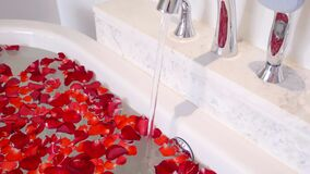 Water Tap in Luxury Marble Bathroom Flowing Water to Bath with Red Rose Petals