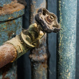 Water Tap. Old rusty water tap in front of blue tubes Royalty Free Stock Image
