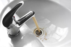 Water Tap With Running Dirty Muddy Water in a Sink. Water tap faucet with flowing contaminated muddy and dirty water in a white bathroom sink Stock Photography