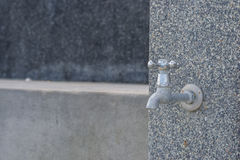Water tap in sand cement wall Royalty Free Stock Images