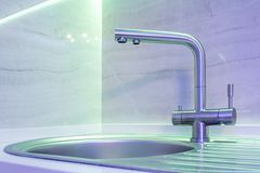 Water tap sink with faucet in expensive loft kitchen in neon light royalty free stock image