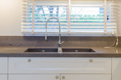 Water tap and sink in kitchen at home Stock Images