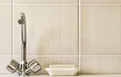 Water taps, and a bar of soap on a background of a tiled wall. Royalty Free Stock Photos