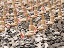 Water taps of fountain court, closeup among gravel. Royalty Free Stock Photo