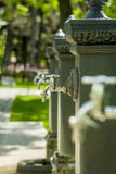 Water taps. In line outside in a park Royalty Free Stock Photos