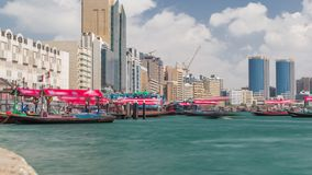 A water taxi boat station in Deira timelapse. Cloudy sky and skyscrapers on background, Here, passengers can board a Dubai Water Taxi to travel around the stock video