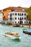 Water taxi and a boat transporting goods, sailing through the Grand Canal in Venice, Italy royalty free stock photos