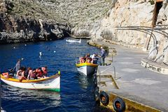 Water taxi departure point, Blue Grotto. Tourists in traditional Dghajsa water taxi boats at the departure point in the bay, Blue Grotto, Malta, Europe Stock Photos