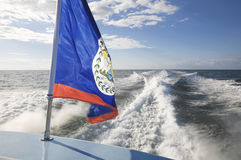 Water taxi from Mexico to Belize. Belize flag on the back of a fast water taxi with wake behind the boat royalty free stock images
