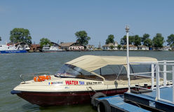 Water taxi. Parked on the bank of river Danube, at Sulina Romania. A  or a water bus, also known as a sightseeing boat, is a watercraft used to provide public Stock Photography