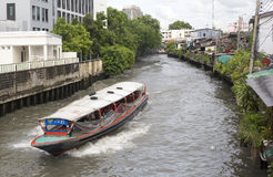 A water taxi races along a canal in Bangkok Stock Photo