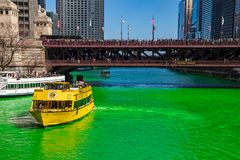 Water Taxi and tour boat on a dyed-green Chicago River as crowds gather on Michicagn Ave. To celebrate St. Patty`s Day stock photography