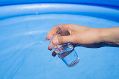 Water testing at swimming pool, laboratory glassware in hand Stock Images