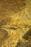 Water texture of golden rocks. Water texture of golden rock patterns from the sunlight royalty free stock image