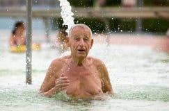 Water therapy. Senior man enjoying waterfall in hot water pool royalty free stock photography