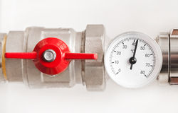 Water thermometer with red valve and metal pipes Royalty Free Stock Photo