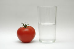 Water and tomat. Red tomat a glass of water stock photography