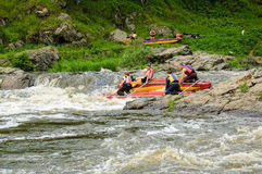 Water tourists move on rapid river in threshold. Beklenischevo, Russia - June 12, 2005: The place with the Iset River rapid current, a so-called threshold the Royalty Free Stock Photo