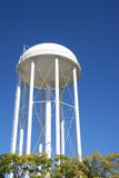 Water Tower. White water tower rising from trees against blue sky Royalty Free Stock Photo