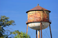 Water Tower. Rusty grungy water tower in the sky Stock Image