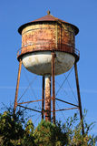 Water Tower. Rusty grungy water tower in the sky Royalty Free Stock Image