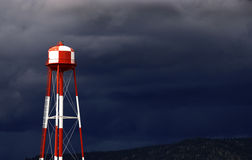 Water Tower. A modern red and white water tower against a cloudy, stormy background Stock Photos