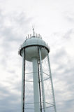 Water Tower Against Cloudy Sky. Small town water tower on a cloudy day Stock Photo