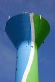 Water tower with cellular phone network antennas. A colourful water tower, painted in blue, green and white, with cellular phone network antennas on top of it Stock Images