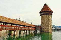 Water Tower Chapel Bridge Lucerne Switzerland. Swans and beautiful riverside buildings on Reuss River bank in Luzern city Switzerland,Chapel bridge and Water Royalty Free Stock Image