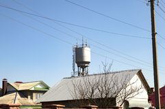 Water tower with mobile communication transmitters against the blue sky stock photos