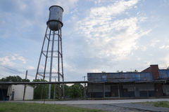 Water Tower near Deserted Warehouse Stock Photo