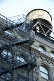 Water Tower. Old fashioned water tower and fire escapes on old buildings like this one in Manhattan in New York City are features that give the city some of its Royalty Free Stock Photo