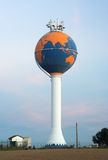 Water tower painted as globe (aerials on top). Water tower painted as globe against an early sunset sky (aerials on top Royalty Free Stock Images