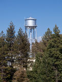 Water tower peeps above tree line Royalty Free Stock Photos